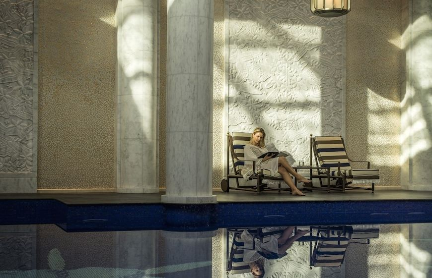 A woman reading by the pool in the Pearl Spa at the Four Seasons Resort Dubai at Jumeirah Beach
