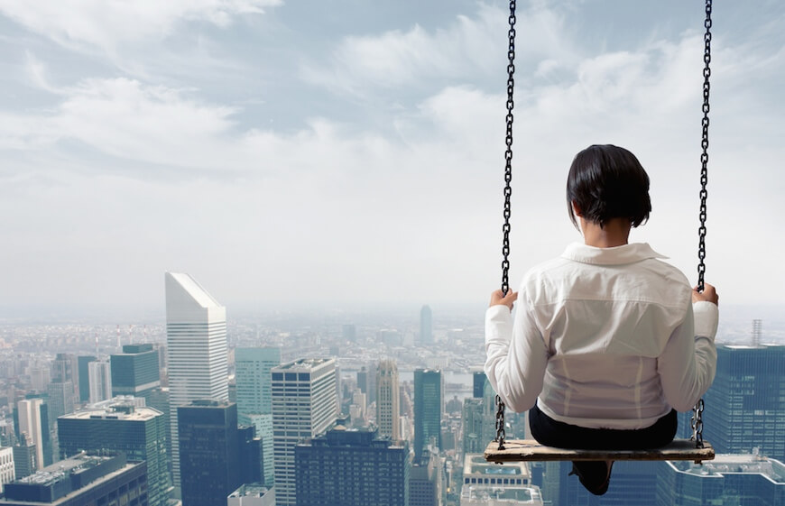 A woman on a swing looking down on a city