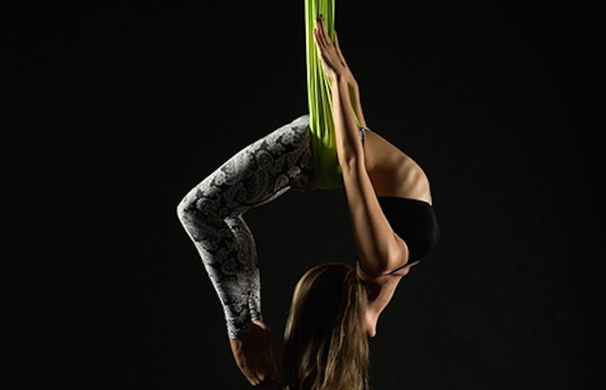 A woman performing AntiGravity Yoga