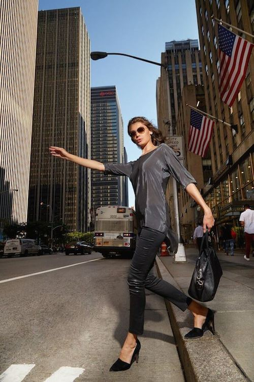 A woman hailing a taxi in New York City wearing anjé clothing