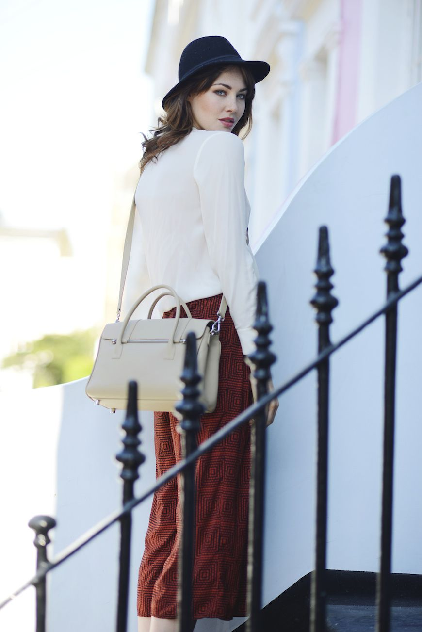 A woman with a Jardine of London handbag in camel standing on some steps