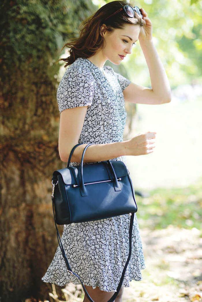 A woman with a Suffolk Blue Jardine of London luxury handbag