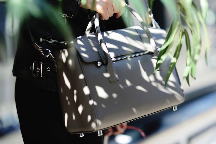 A woman holding a taupe Jardine of London luxury handbag