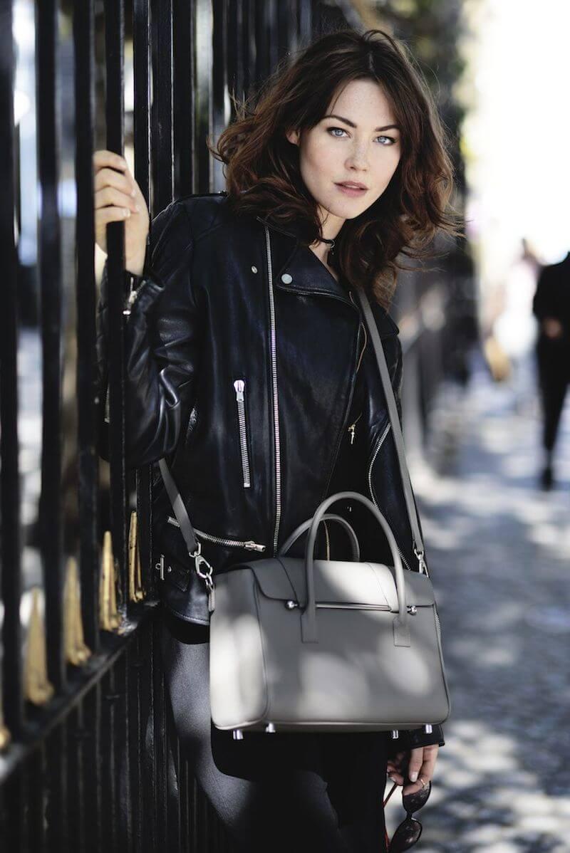 A woman with a taupe Jardine of London handbag