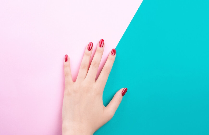 A womans hand with painted red nails
